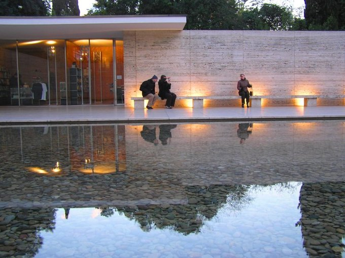 An image of the exterior of the Barcelona Pavilion. Three people sit on a bench outside. The exterior wall is simple and there are glass doors leading inside. In the foreground is a clear pool over many rocks.