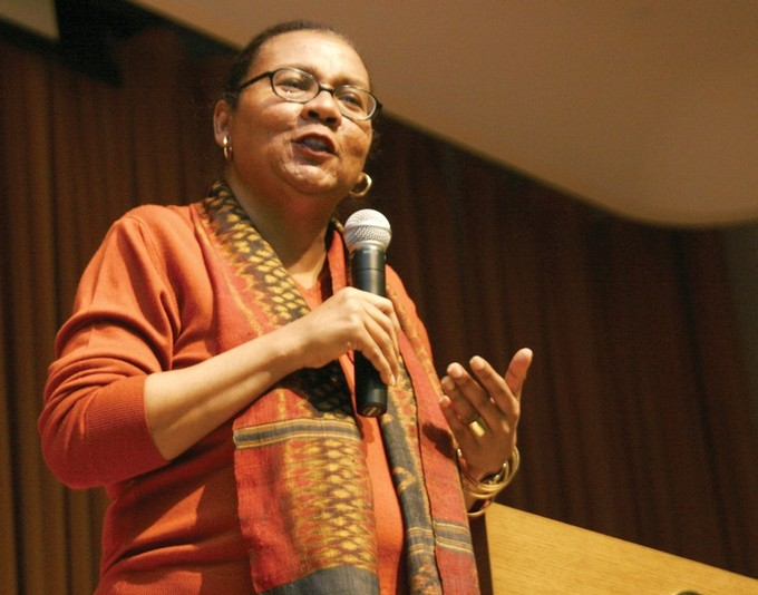 A photo of bell hooks speaking into a microphone.