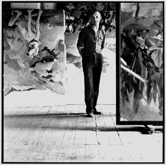 A photo of Georg Baselitz standing amongst his art.