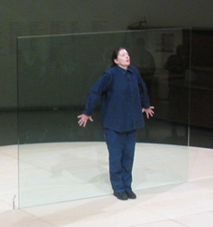 A photo of Marina Abramovic standing in front of a glass pane as part of a performance art.