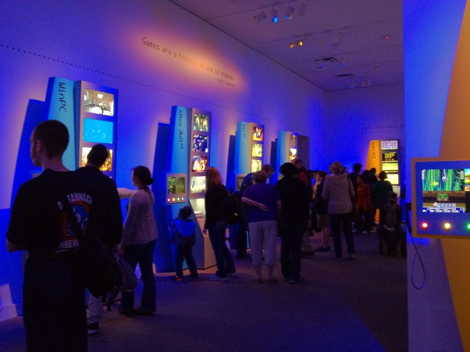 People walk through a dark gallery of video games that are displayed on the walls.