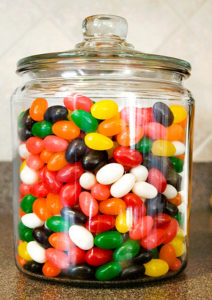 A glass jar full of different colored jelly beans.
