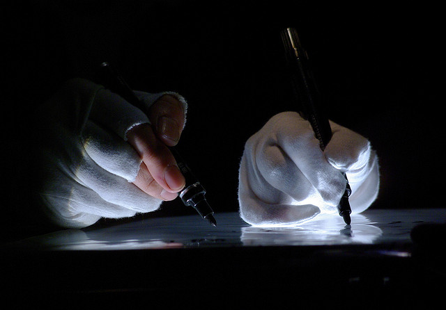 Photograph of two hands writing next to each other, holding black pens and wearing white gloves