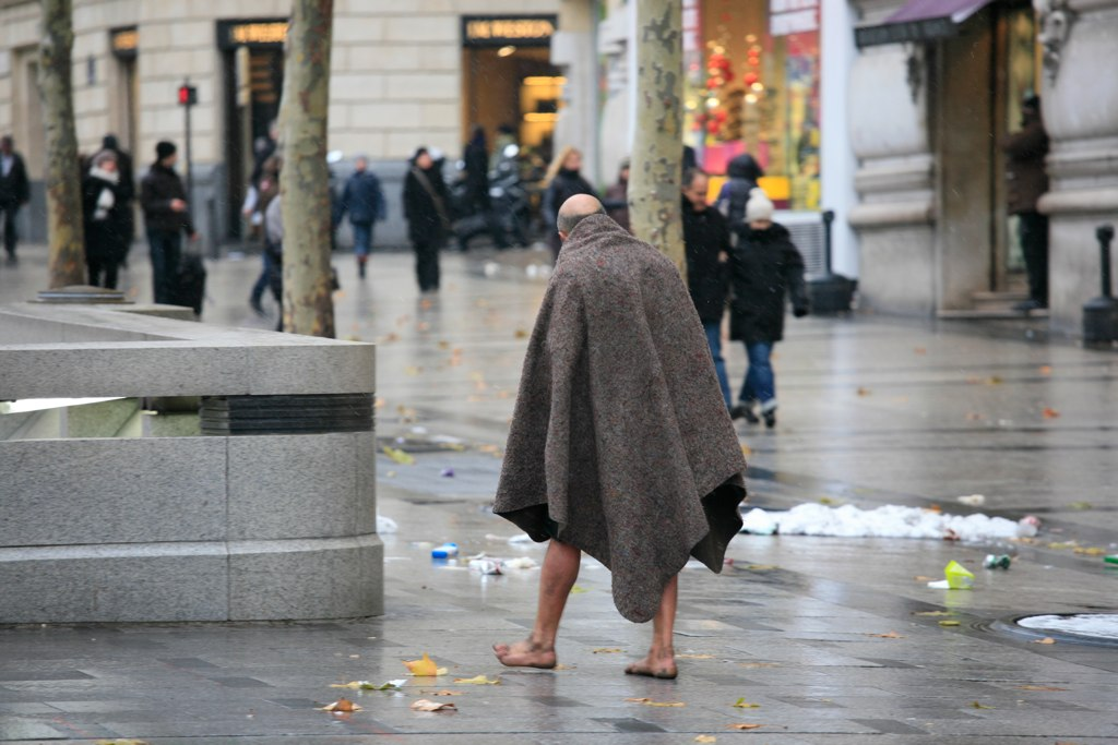 Homeless man wearing a blanket with barefeet walking on a cold street, with others walking around in heavy coats.