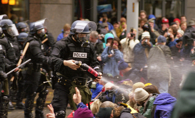 An armed policeman sprays tear gas into a group of protestors.