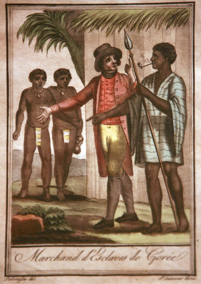The drawing depicts a European slave trader and an African slave trader discussing the sale of two male slaves who are standing in the background. The slaves' feet are shackled together.