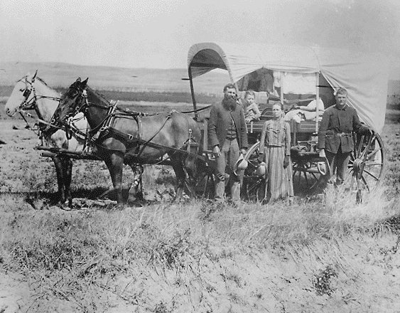 A family poses with the wagon in which they live and travel daily during their pursuit of a homestead.