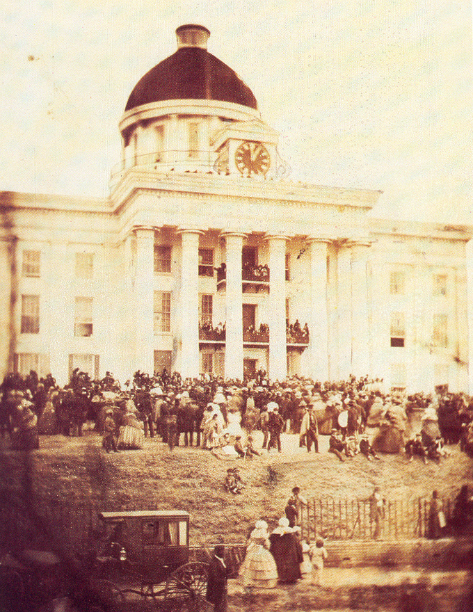 The photograph depicts a large crowd of people gathered in front of the Alabama capitol building.
