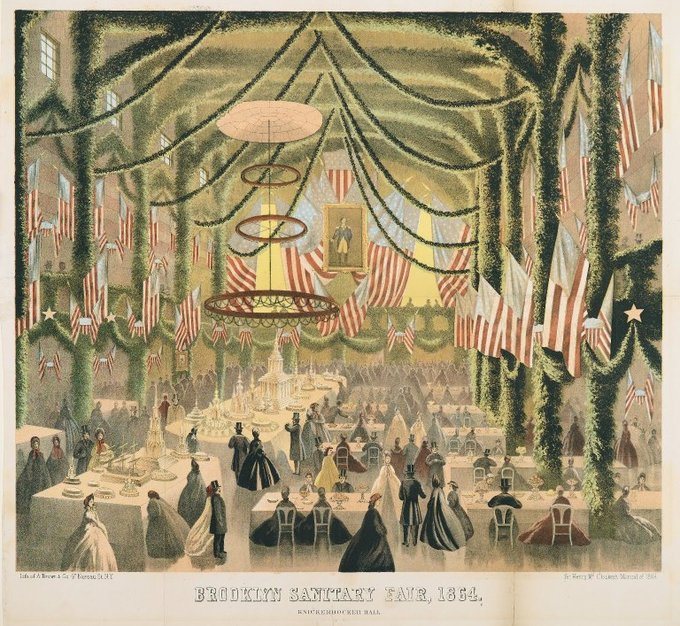 The lithograph shows a large, elaborately decorated room filled with dining tables, well-dressed men and women, American flags, and green boughs.