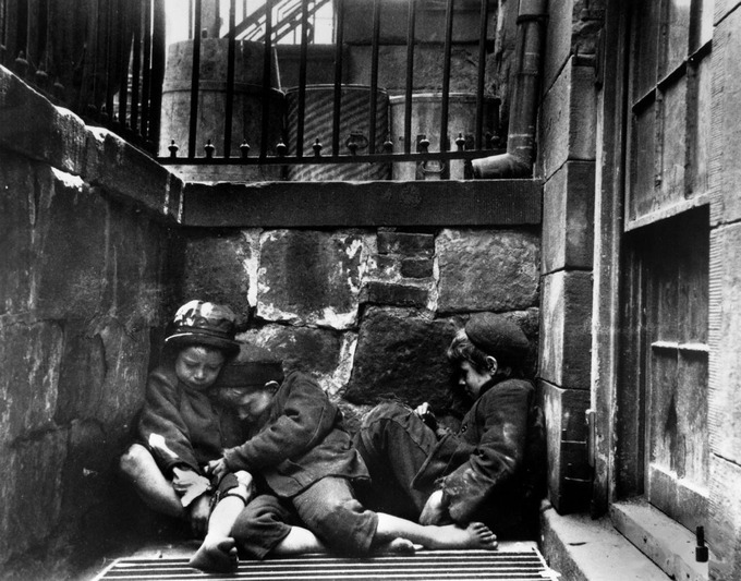 The photograph shows three poor children without shoes sleeping huddled up against each other in the street.