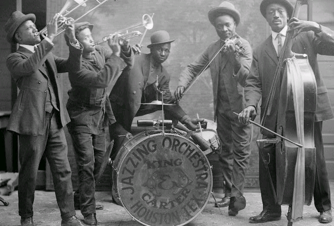 "The photograph shows a trombonist, a trumpeter, a drummer, a violinist, and a bassist. The drum set says ""King & Carter Jazzing Orchestra, Houston Tex"" on it."