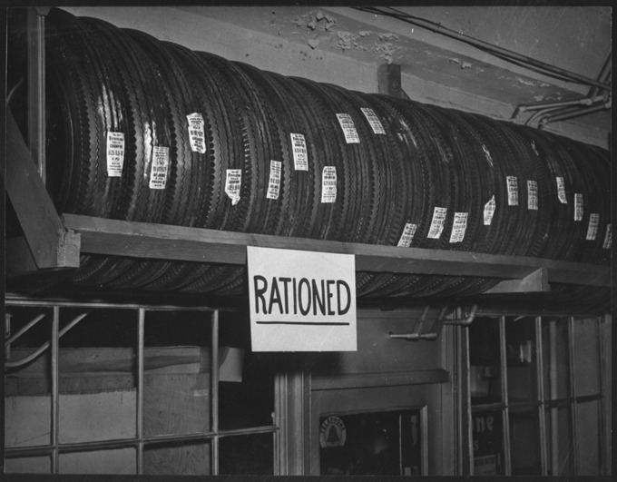 "The black and white photograph shows a shelf of Firestone tires. A sign that says ""Rationed"" is affixed to the shelf."