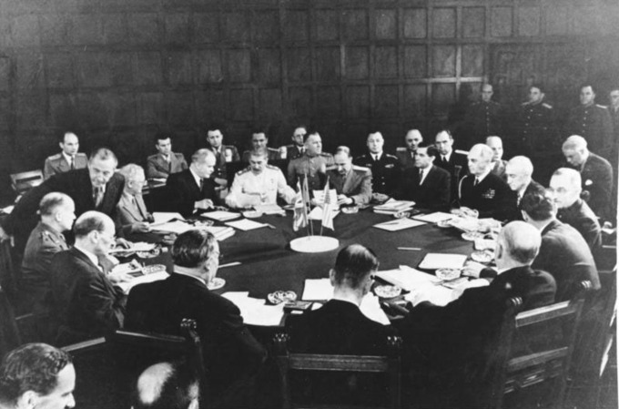The photograph shows the leaders of the major Allied powers seated at a round table.