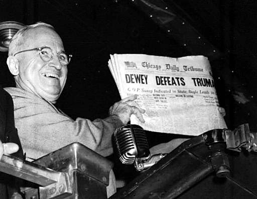 Truman smiles as he holds up the newspaper with the incorrect headline.