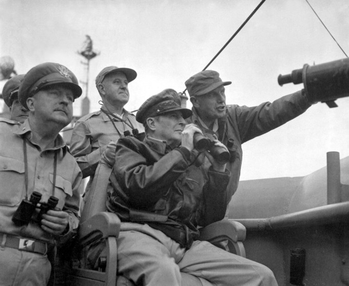 Photograph of Brigadier General Courtney Whitney, government section, Far East Command; General Douglas MacArthur, Commander-in-Chief, United Nations Command, and Major General Edward Almond, Commanding General, X Corps in Korea, observing the shelling of Incheon from the USS Mount McKinley.