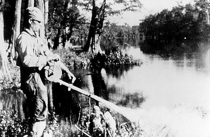 A photograph of a man spraying DDT on the bank of a river.