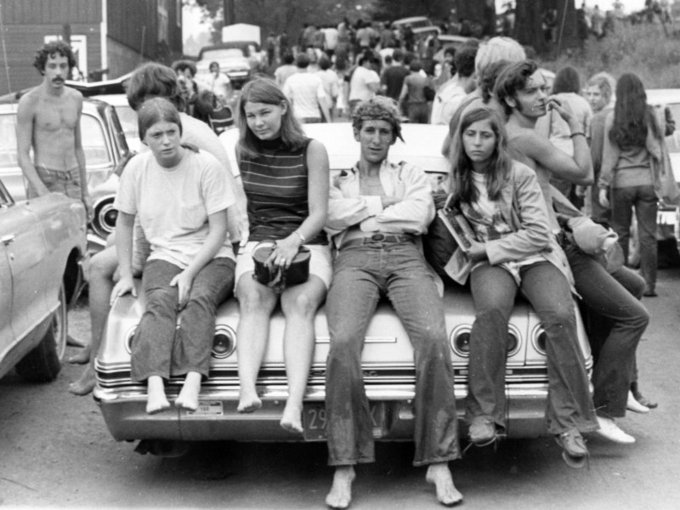 Young men and women sitting on the trunk of a car