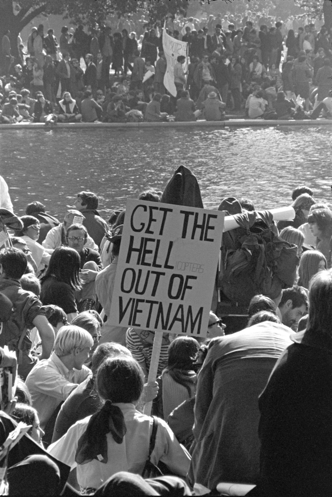 "The photograph shows a large crowd of protesters. One holds a sign that reads ""Get the Hell(icopters) out of Vietnam."""
