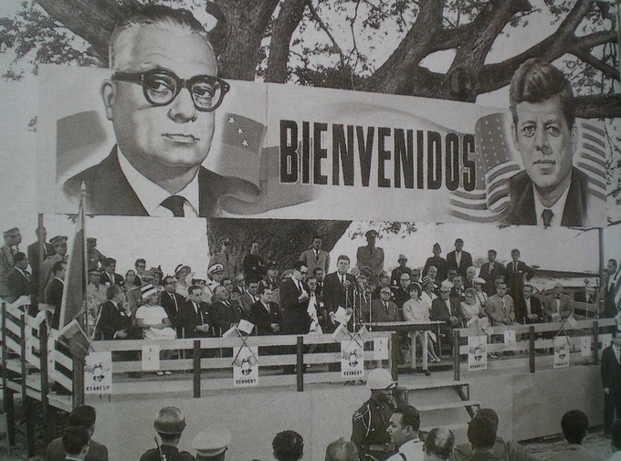 """A large billboard over the stage reads """"Bienvenidos"""" and is bookended with portraits of John F. Kennedy and Rómulo Betancourt."""