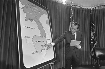 The photograph shows Nixon standing next to a large map of a portion of southeast Asia. He is pointing at Cambodia as he speaks.