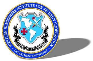 "The logo includes the image of shield displaying a map of North and South America, a cross pattée, and a lit torch crossed with a sword. A ribbon with the words ""Libertad Paz y Fraterndad,"" appears below the the shield. The shield and ribbons are surrounded by the name of the agency, ""Western Hemisphere Institute for Security Cooperation"" and ""Department of Defense."""
