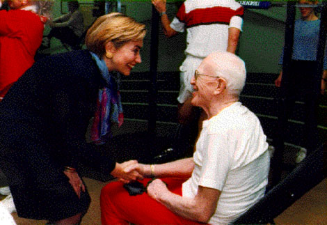 First Lady Hillary Clinton shaking hands with an elderly man