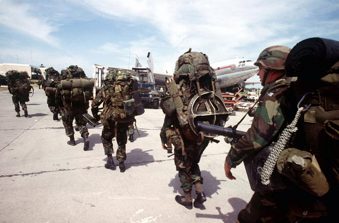 Seven armed soldiers carry their gear towards a plane.