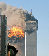 The image shows the twin towers of World Trade Center engulfed in flames and smoke.