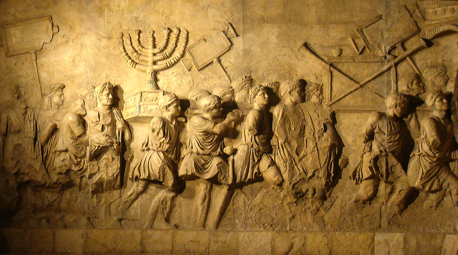 A stone relief showing Roman soldiers carrying treasure from the sack of Jerusalem, including a menorah.