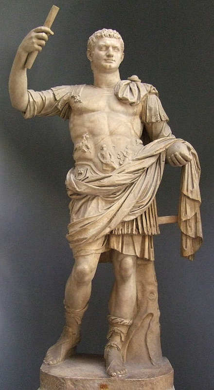 An image of a full-body statue of Domitian holding up his right hand with a scroll.