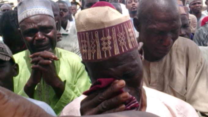 The photograph shows three men in a crowd crying and praying.