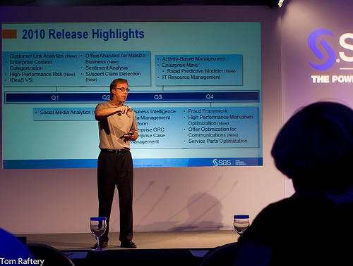 A man standing on a stage during a presentation. A PowerPoint slide is displayed on a projector behind him.