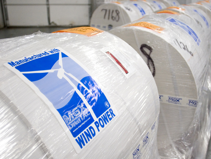 "Large rolls of industrial paper that are packaged with a label that says ""Manufactured with Wind Power."""