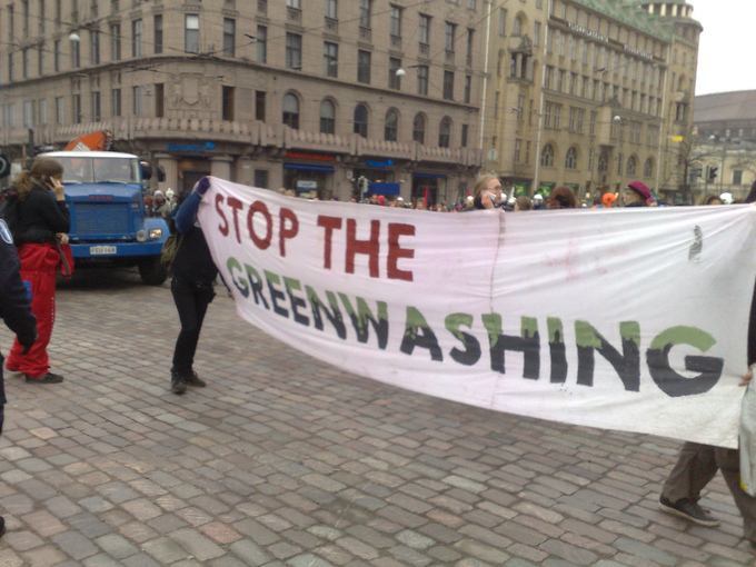 "Protestors in a street hold up a sign that says ""Stop the Greenwashing."""
