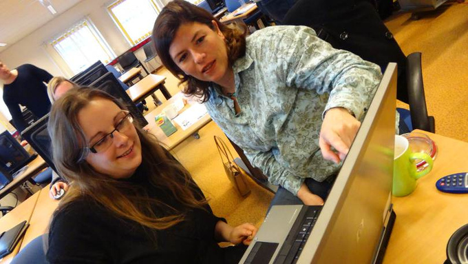 Two women look at a laptop and discuss information that is on the screen.