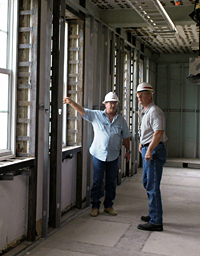 Two engineers in hard hats stand inside a building that's under construction and discuss the work.