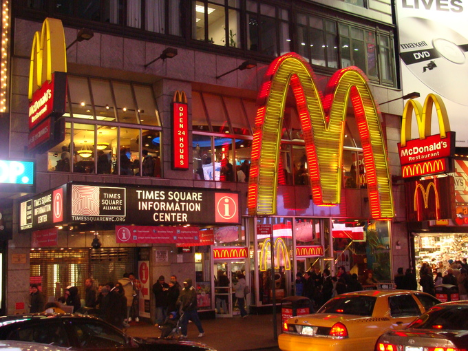 A large McDonalds with light-up signs around it in a city center