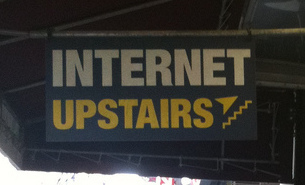"A sign that says ""Internet upstairs."""