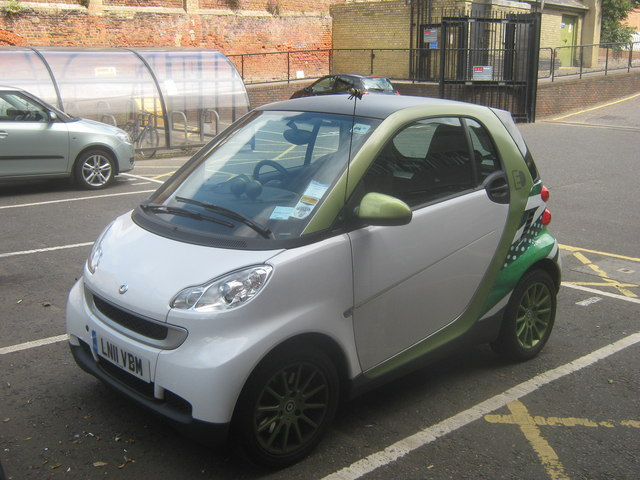"A ""smart"" car, which is small, and white and green"