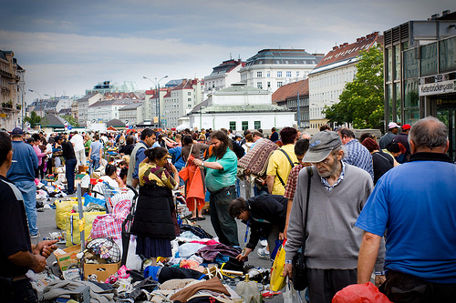 an open market in Vienna with many people crowding the streets.