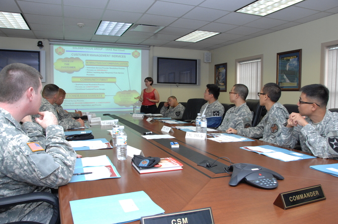 A group of soliders sits around a table while a woman discusses a PowerPoint presentation at the front of the room.