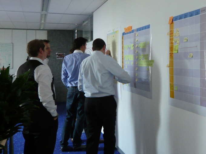 A group of businessmen work on a series of plans that are displayed on an office wall.