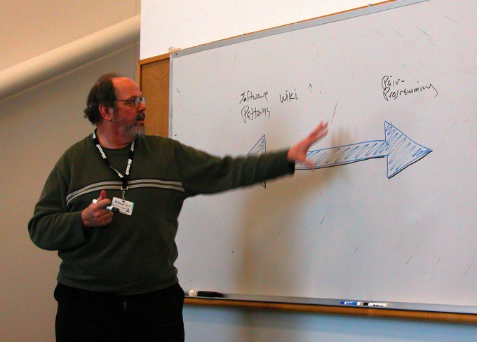A man gives a presentation and discusses information on a dry erase board.