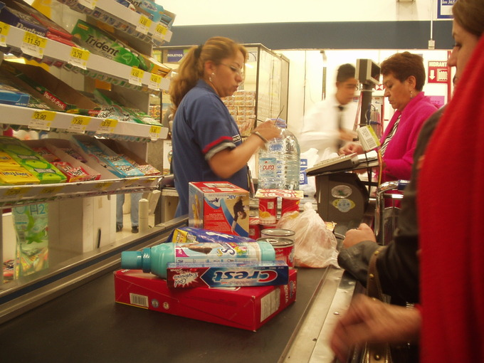 A woman scans the items in a populated grocery store line