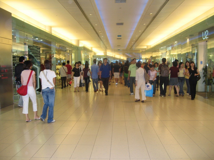 people walking around the hall of a shopping mall with stores around