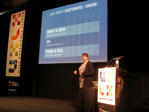 A woman stands on a stage and discusses a PowerPoint slide that breaks down customers wants and needs.
