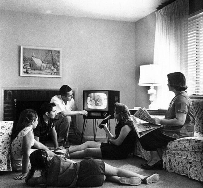 A family sits in the living room and watches television.
