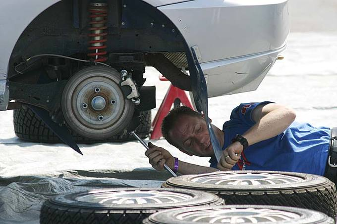 A man fixing a car from underneath