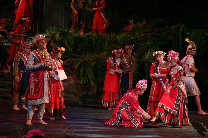 Cultural performers take part in a show on a large stage.