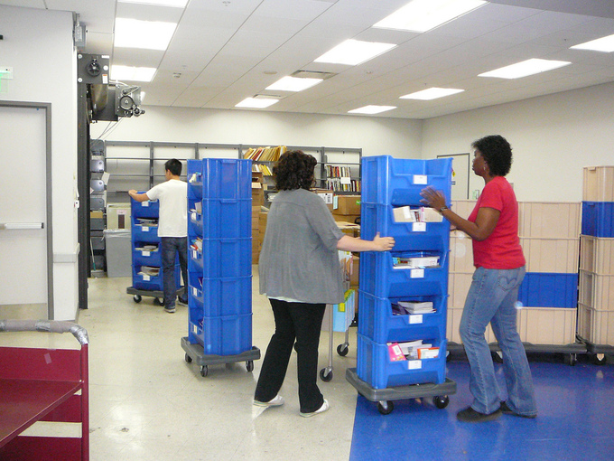 Three people move containers of goods in a supply room.